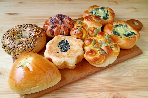 Assorted buns and pastries on wooden tray served on wooden table Premium Photo