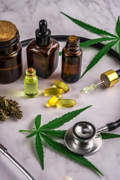 Assorted cannabis products, pills and cbd oil over medical prescription sheet Premium Photo