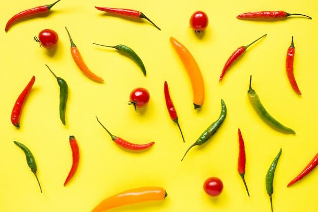 Assorted chili pepper tomato cherry on yellow bright background Premium Photo