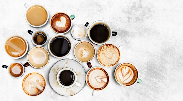 Assorted coffee cups on a textured background Free Photo