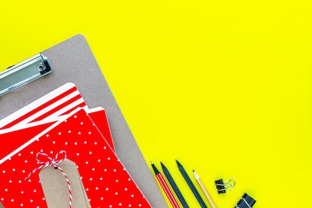 Ассорти красочные канцелярские товары для школы и офиса на желтом фоне с copyspace. Бесплатные Фотографии