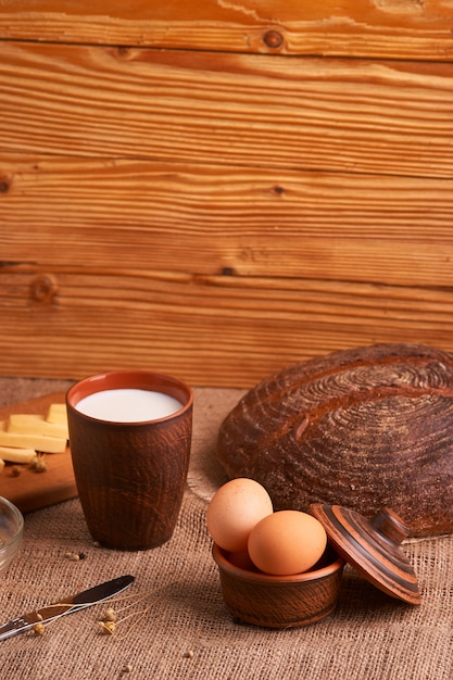 Assorted dairy products milk, cheese, eggs. rustic still life on table Premium Photo