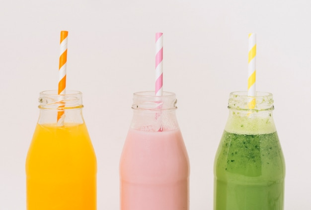 Assorted delicious fruit smoothies in bottles with straws Free Photo