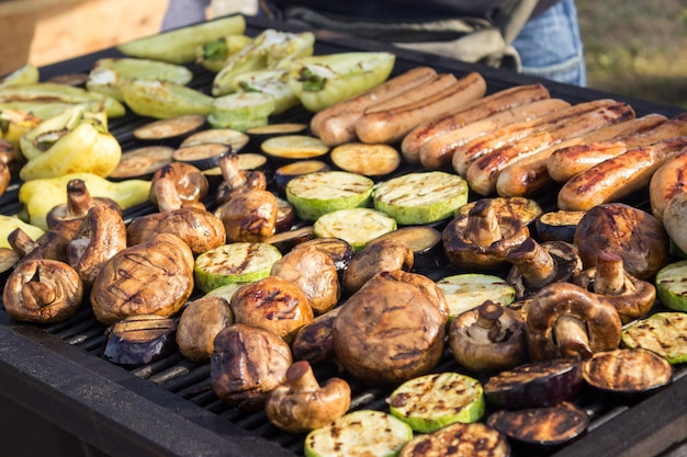 Assorted delicious grilled meats with vegetables over the barbecue on the charcoal. Premium Photo