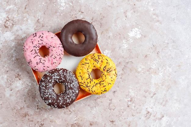 Ассорти десертов с шоколадной глазурью, розовой глазурью и посыпкой. Бесплатные Фотографии