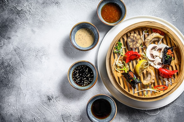 蒸し器での点心の盛り合わせ。中華料理のセットです。灰色の背景。上面図。コピースペース Premium写真