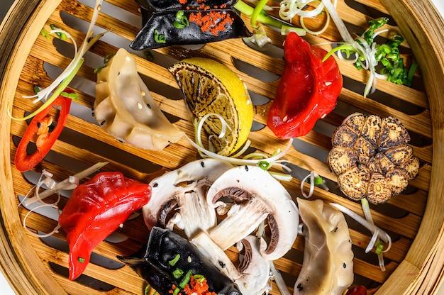 蒸し器での点心の盛り合わせ。中華料理のセットです。灰色の背景。上面図 Premium写真