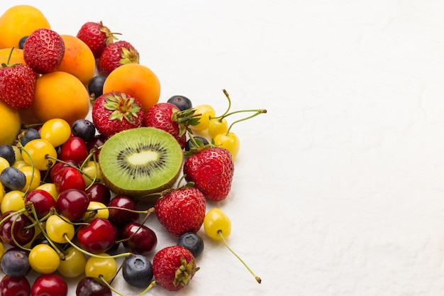 Assorted fresh berries and fruits. apricots kiwi strawberry cherry blueberry on white background. weight loss concept top view. copy space. Premium Photo