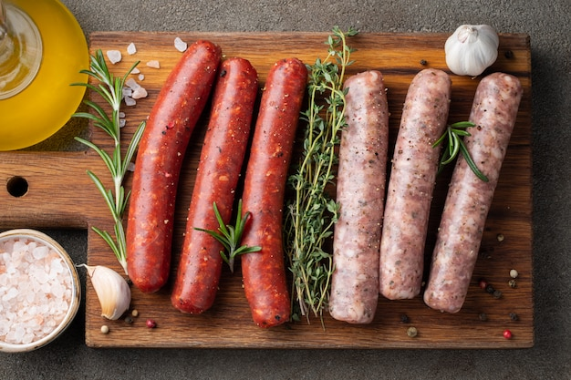 Assorted fresh sausages with thyme, rosemary. Premium Photo