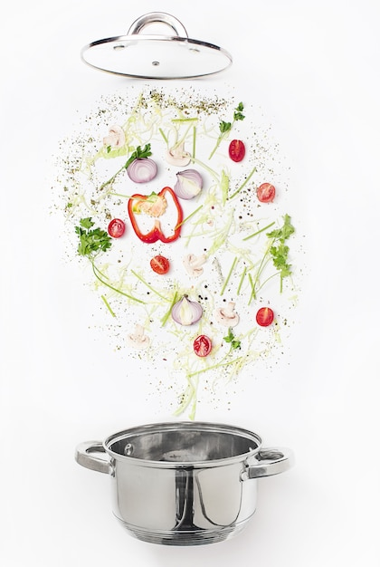 Assorted fresh vegetables falling into a bowl Free Photo