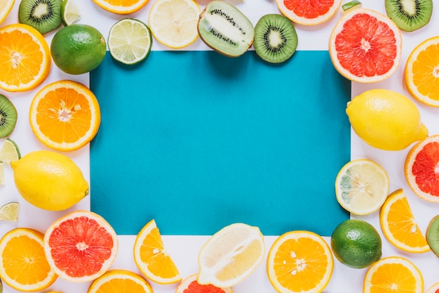 Assorted fruits around blue paper sheet Free Photo