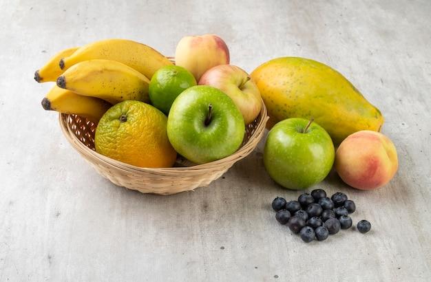 ライトグレーのテーブルの上にバスケットに入ったフルーツの盛り合わせ。 Premium写真