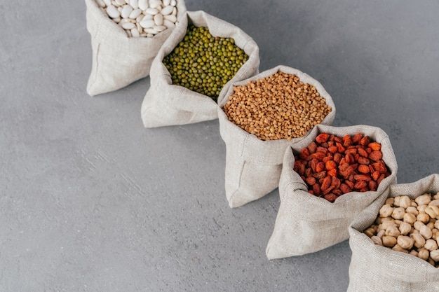 Assorted gluten free grains in linen cloth bags on grey background. Premium Photo