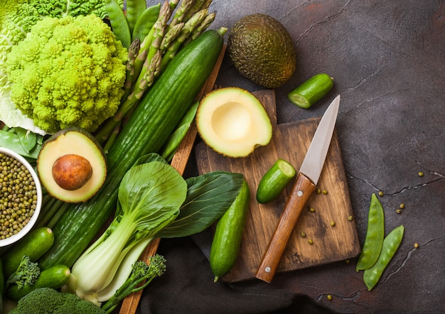Assorted green toned raw organic vegetables in wooden box on dark stone Premium Photo
