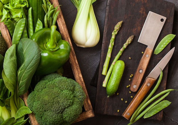 Assorted green toned raw organic vegetables in wooden box Premium Photo