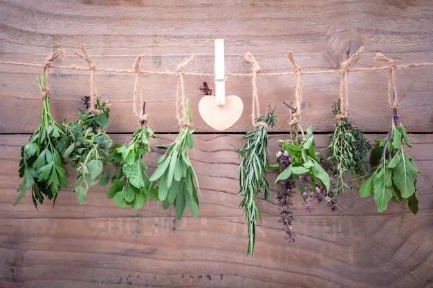 Ассорти вешающих трав на деревенском старом деревянном фоне. Premium Фотографии