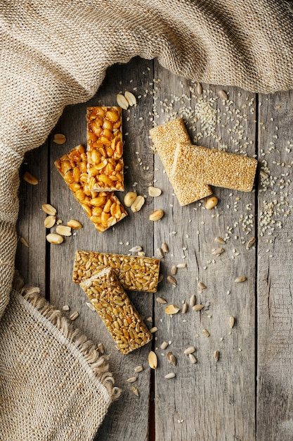 Assorted kozinaki,, with burlap fabric. country style. delicious sweets from the seeds of sunflower, sesame and peanuts, covered with shiny glaze. Premium Photo