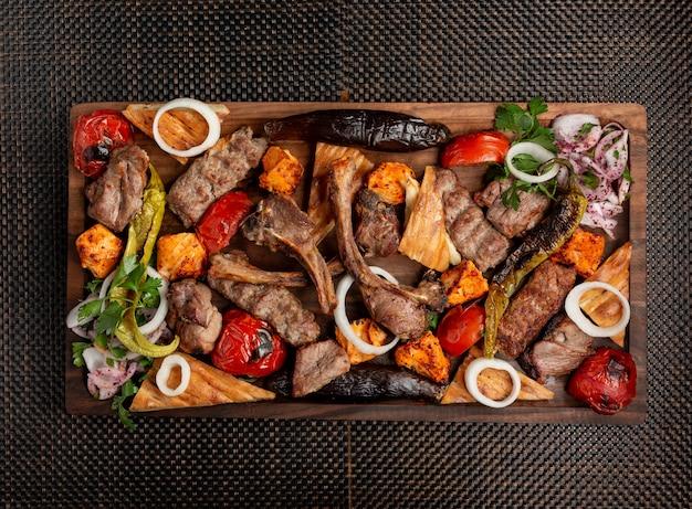 Kebab di carne assortito con erbe cipolle e verdure grigliate Foto Gratuite
