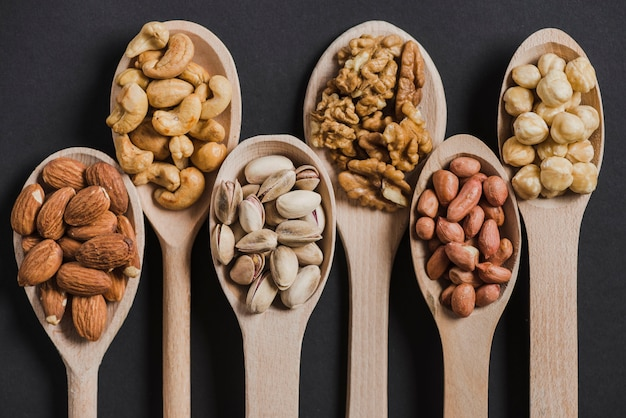 Assorted nice nuts in wooden spoons Free Photo