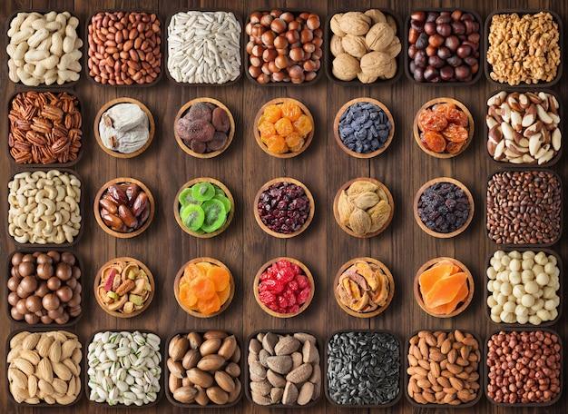 ナッツの盛り合わせと木製のテーブル、上面にドライフルーツ。ボウル、食品背景で健康的なスナック。 Premium写真