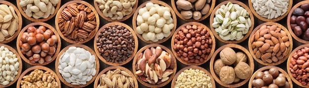 Assorted nuts background, vegetarian food in wooden bowls, top view Premium Photo
