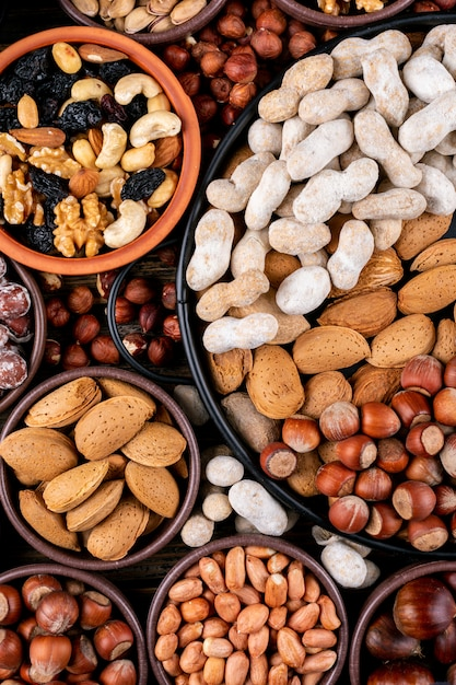 Assorted nuts and dried fruits in a different bowls and plates with pecan, pistachios, almond, peanut, cashew, pine nuts top view Free Photo