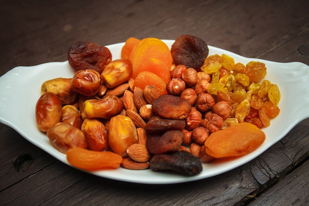 Assorted nuts and dried fruits in white plate. Premium Photo
