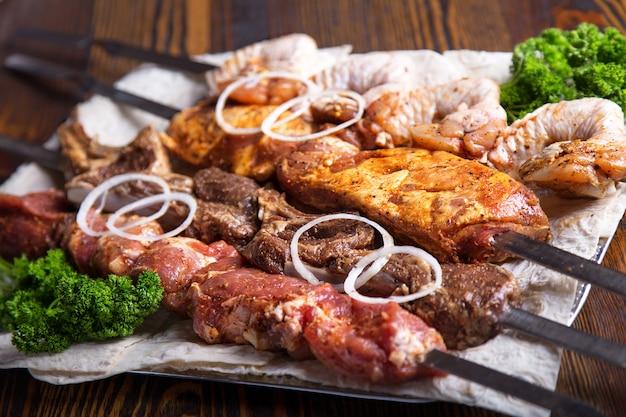 Ассорти из мяса на шпажках. сырая свинина, телятина и курица готовы приготовить. sashlik Premium Фотографии