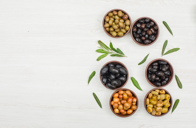 Assorted olives with olive tree leaves in a clay bowls on white wood, flat lay. Free Photo