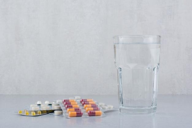 Confezioni assortite di capsule e pillole con bicchiere d'acqua. Foto Gratuite