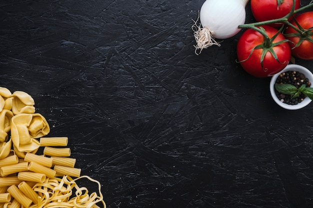 Assorted pasta near vegetables and spices Free Photo