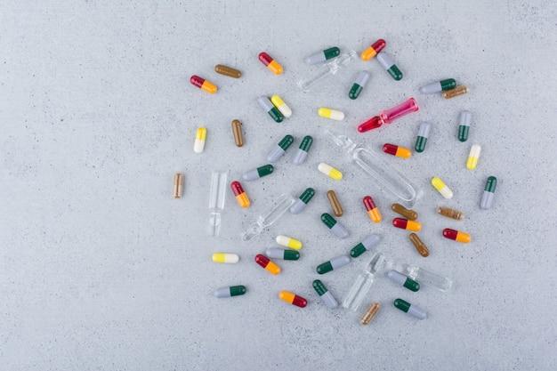 Ассорти фармацевтических капсул и ампул на мраморной поверхности. Бесплатные Фотографии