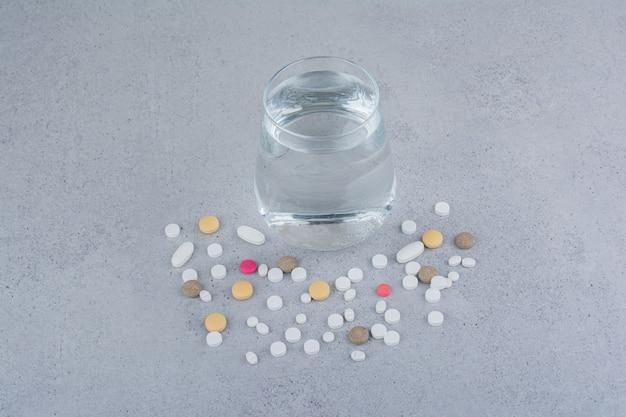 Assortimento di pillole di medicina farmaceutica e bicchiere d'acqua. Foto Gratuite