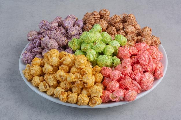 Caramelle assortite di popcorn servite in piccole ciotole di vetro su marmo. Foto Gratuite
