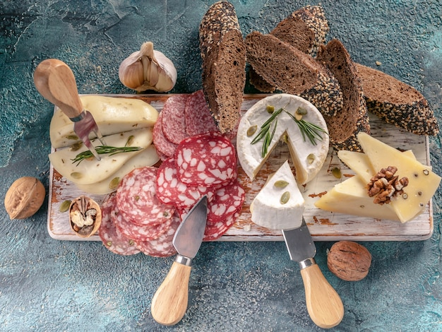 Assorted sausages and cheese with bread on wooden board Premium Photo