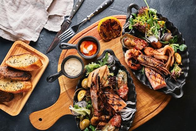 シーフード盛り合わせ。提供されるシーフードテーブル、イカ、エビ、サーモンステーキ、タコの美しい構図。 Premium写真