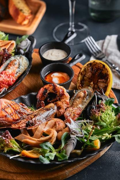 盛り合わせのシーフード盛り合わせ盛り合わせシーフードテーブル、イカ、エビ、サーモンステーキ、タコの美しい構成 Premium写真