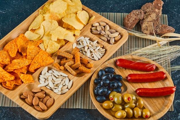 木製のテーブルに盛り合わせのスナック、ソーセージ、キャビア、オリーブのプレート。 無料写真