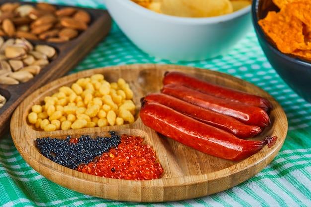 Spuntini assortiti, ciotola di patatine e un piatto di salsicce su un tavolo blu. Foto Gratuite
