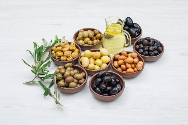 Assorted variety of olives in a clay bowls with olive leaves and a jar of olive oil high angle view on white wood Free Photo