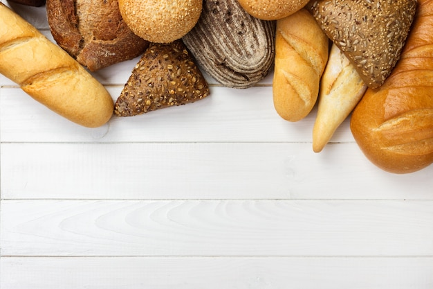 Assortment of baked bread on wooden table background. Premium Photo