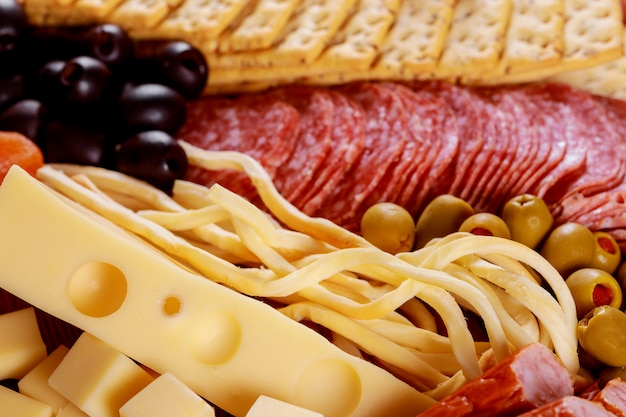 Assortment of cheese and olives on salami sausage table Premium Photo