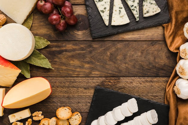 Assortment of cheeses; grapes; bread slice; walnut on dark wooden table Free Photo