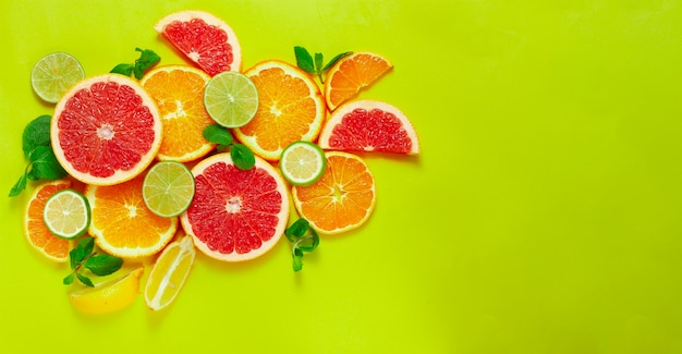 Assortment of citrus fruits, on a yellow background, top view, no people, horizontal, Premium Photo