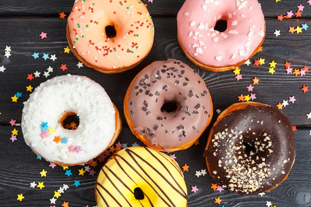 Assortment of colorful donuts decorated with colorful confetti sprinkles on dark wooden Premium Photo