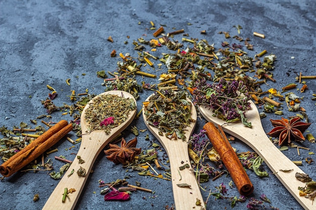 Assortment of differentdry tea in wooden spoons with anise and cinnamon in rustic style Premium Photo
