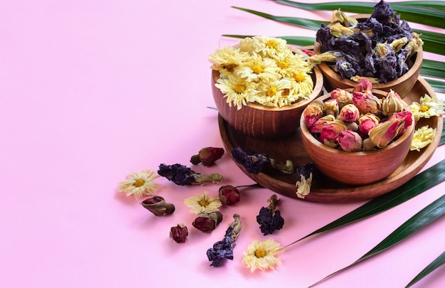 Assortment of dry herbal healthy tropical tea in wooden bowls on pink background. Premium Photo