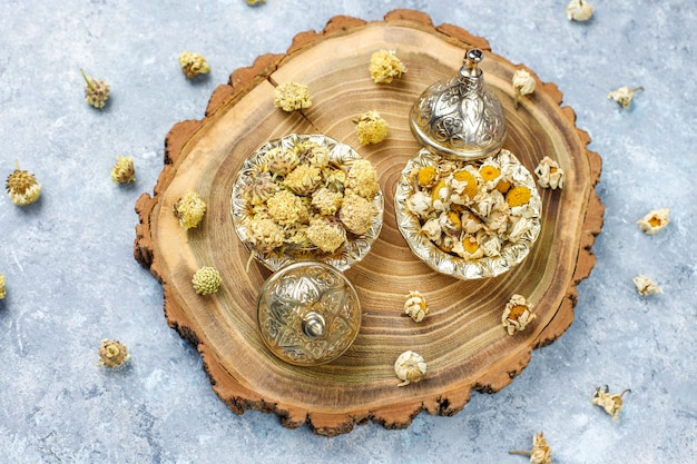 Assortment of dry tea in golden vintage mini plates. tea types Free Photo