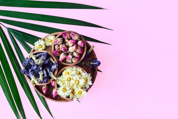 Assortment of dry tea in wooden bowls isolated on pink background. Premium Photo
