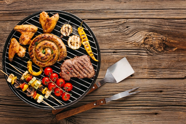 Assortment of marinated meat and sausages grilling on barbecue grill over wooden background Free Photo